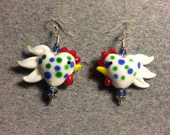 White with blue and green spots heart shaped lampwork rooster bead earrings adorned with blue Czech glass beads.
