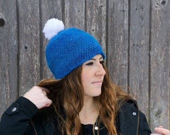 Crocheted blue hat with white pompom
