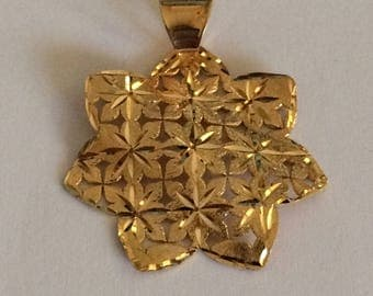 Flower shaped pendant in yellow 18k gold.