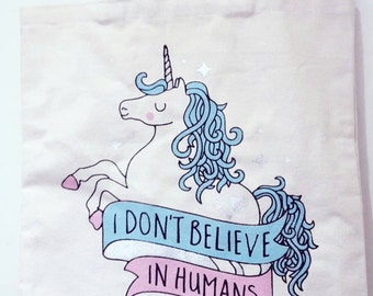 I don't believe in humans unicorn tote bag.