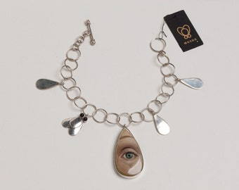 CRY ME A RVER, Silver Charm bracelet with hand painted eye, silver tears and a fly. The painted image of a crying eye is melancholy and fab.