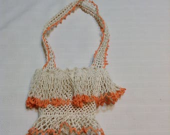 Vintage mid century thread crochet basket in off white and an orange/peach color, starched.