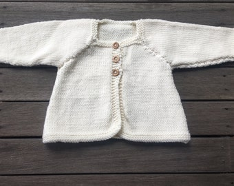 Baby cardigan with wooden buttons. 100% super soft machine washable merino wool. Size newborn to 6 months.