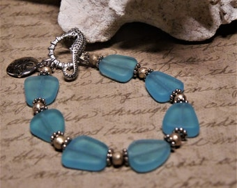 Pacific Blue sea glass bracelet with Ethiopian silver beads, silver sanddollar charm, and Seahorse toggle clasp