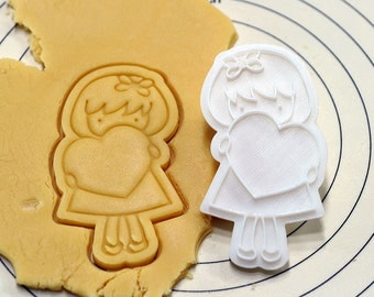 Girl Holding Heart Cookie Cutter and Stamp