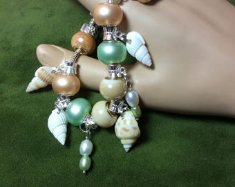Genuine Pearl charms and sea shell beaded bracelet! A very pretty bracelet made with green and white pearls along with sea shells.