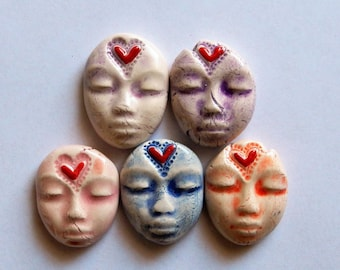 5 ceramic faces with red hearts on their foreheads