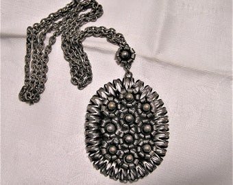 Vintage Ornate Silver Pendant and 24 Inch Chain. The 2 Inch Oval Shaped Pendant Has FLowers In the Center and a Pierced Metal Edge. (D12)