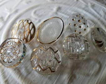 Vintage Buttons - lot of 7 assorted clear glass  gold hand painted medium size pressed glass  designs.  ( mar 121 17)