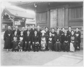 Vintage black and white photo of a group of Japanese  men and women in front of building