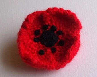 Small hand knitted red poppy flower brooch.  Black centre.