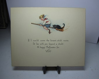 Unused 1920's halloween greeting card little boy in sailor style shirt flying on a witches broom with a black cat
