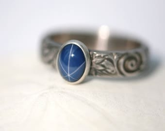 Medium Oval Blue Star Sapphire and Sterling Silver Ring on Floral Pattern Band in Antique Silver Finish