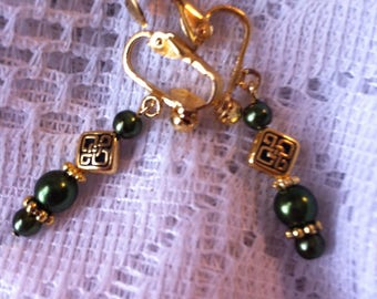 Dark green luster and gold plated clip on earrings with Celtic knot beads