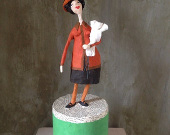 Papermaché doll Mrs Dalloway on a tin