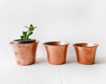 A set of 3 hammered copper plant pot holders