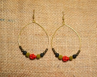 Ethnic earrings on gold base with lava rock beads and red skulls.