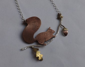 Copper Squirrel on a silver branch with brass oak leaves and acorn.