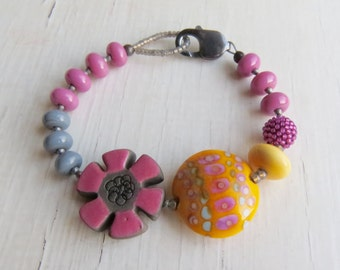 Sunshine - handmade artisan bead bracelet in warm rose pink, sunshine yellow and grey with flower  - Songbead, UK, narrative jewellery