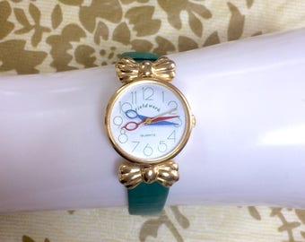 Vintage Field Work red and blue scissors design watch hands wrist watch with golden bow and green leather belt. Rare and unique.