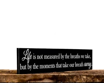 Inspirational sign - Life is not measured by the breaths we take wooden sign pictured in black