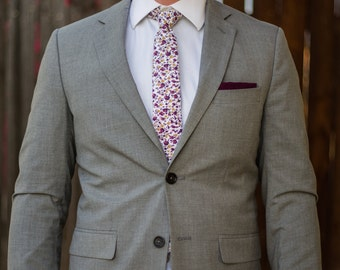 White skinny tie with maroon, pink, and mustard yellow floral pattern