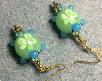 Light green and turquoise lampwork turtle bead dangle earrings adorned with light green Czech glass beads.