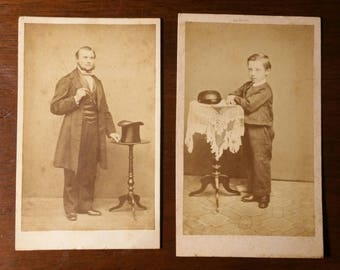 Set of 2 CDV photos of a father and a son with their hats on the table