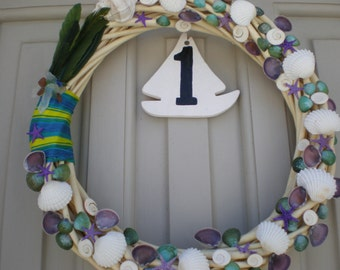 Decorative wreath with colored shells, feathers, and thread,