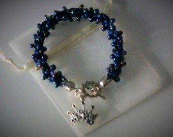 Blue kumihimo bracelet with seed beads, ornamental lock and charm.