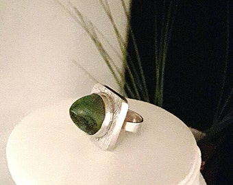 Modernist silver ring with a green stone.