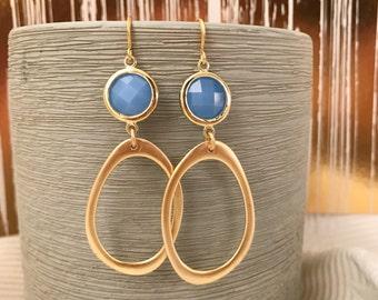 Gold asymmetrical oval earrings ice blue stone