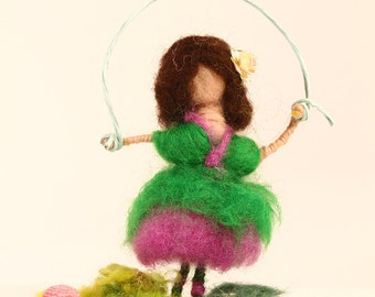 Girl playing with rope on a wooden surface, needle felted doll, waldorf inspired.