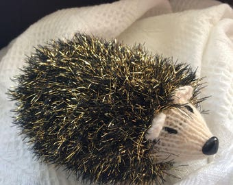 Hand knitted hedgehog soft toy plushie.
