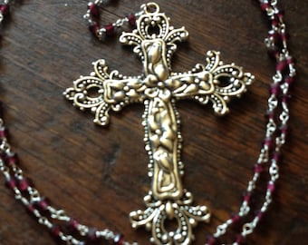 Ornate silver cross necklace rosary with garnet rosarychain and ornate center piece.