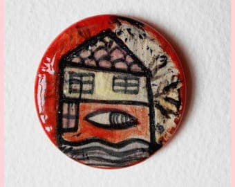 Ceramic house brooch of a house with an eye inside and textured background