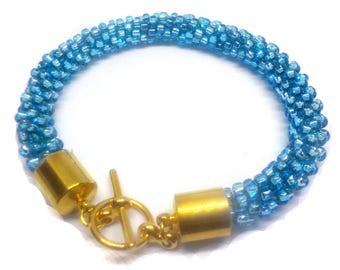 Pretty light blue  bracelet beaded  on a Kumihimo braid