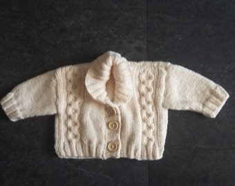 Handknitted cream aran jacket in size 0-3 months.