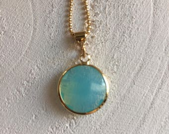 Gold-coloured ballchain necklace with an aqua blue crystal glass pendant.