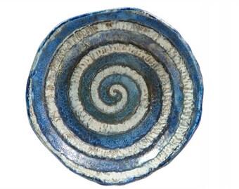 Raku ceramic with decorative centerpieces to spiral, irregular border