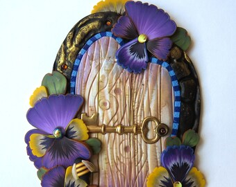 Purple Pansies with a Bumble Bee Fairy Door by Claybykim Pixie Portal Polymer Clay Miniature Door for Fairy Gardens and Home