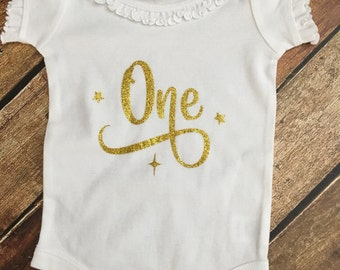 "Cute little bodysuit with a ""One"" done in glitter  vinyl . This can be done in long sleeves if you prefer, just leave me a note.."