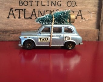 London Taxi Carrying White Christmas Tree Ornament