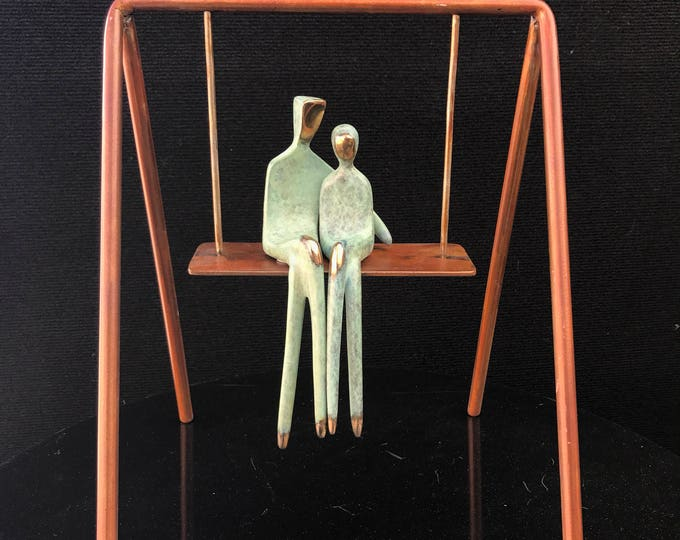 "Swing with me, custom bronze sculpture couple sitting on a swing. 12"" tall stainless steel swing. Available as is or in brown patina."