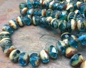 25 Czech Glass beads Color: Transparent capri blue and ivory, picasso finish around the hole.