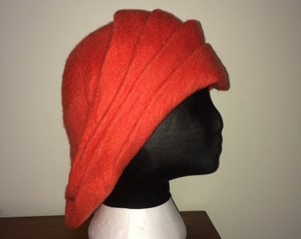 A beautifully soft persimmon colored wet felted merino wool hat