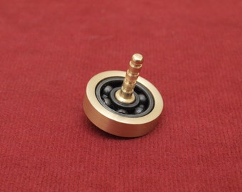 Spinning top, roller bearing and brass EDC