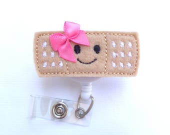 Badge Reel Retractable - Stick it - Smiley face pink bow - tan felt band aid - Nurse badge reel school nurse pediatrician medical badge reel