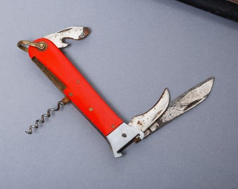 Vintage metal folding knife with bottle opener, metal with plastic handle, rustic patina