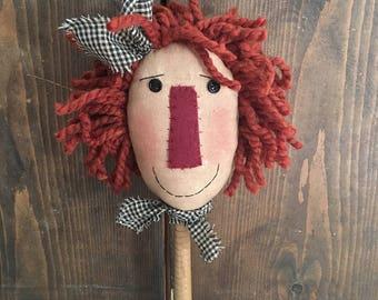 raggedy annie doll on wooden bobbin